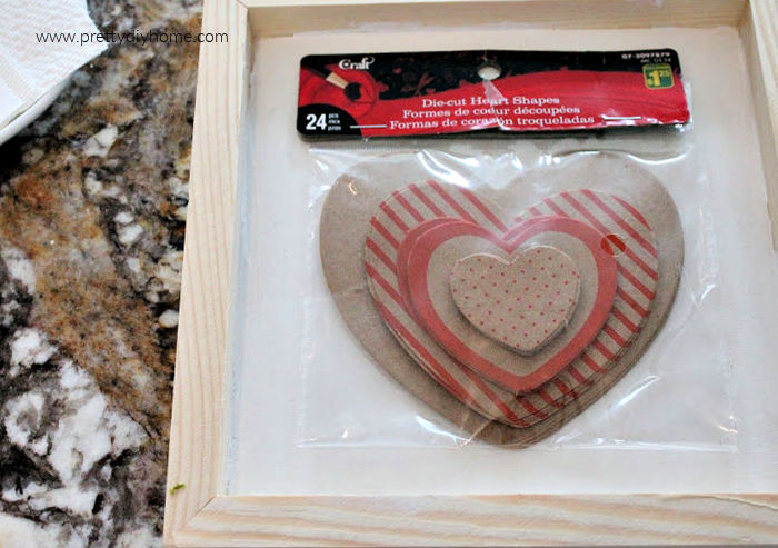 A package of dollar store paper valentines sitting on a frame; The supplies for making a simple farmhouse Valentine craft.