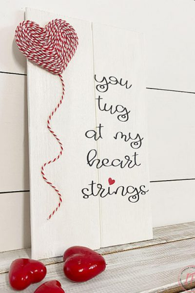A DIY wood Valentine Sign that says you tug at my heart Valentine.