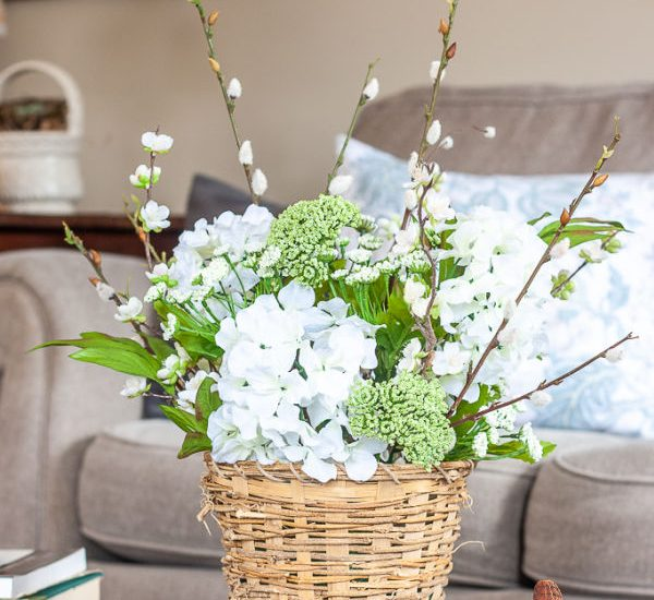 A spring centerpiece made with green and white faux flowers and a basket.