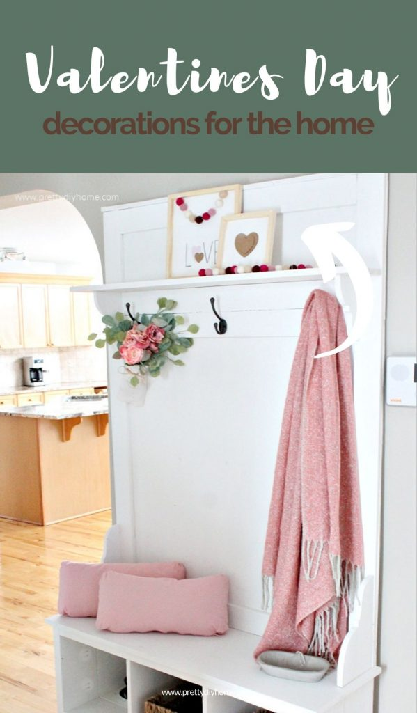 A front foyer farmhouse tree decorated with two DIY Valentine signs pink flowers a pink shall and two pink pillows.