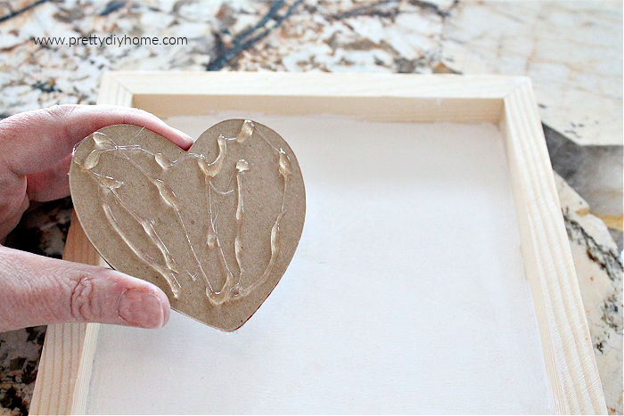 A stack of brown Valentines being applies to a farmhouse frame using hot glue.