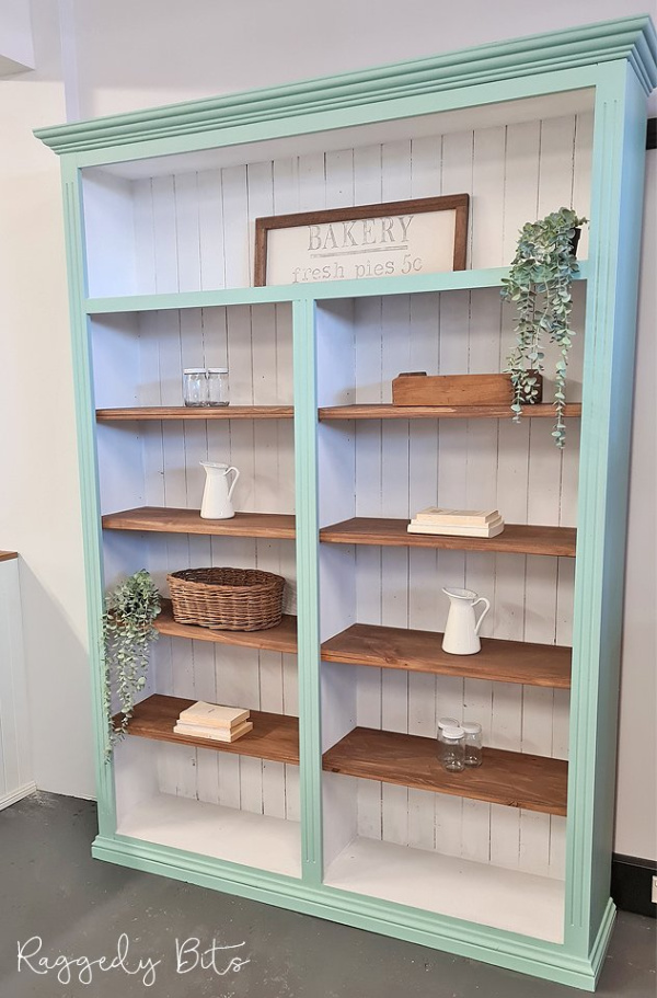 Old wood bookshelf makeover into farmhouse book shelves in white with a soft mint finish and light brown shelves.