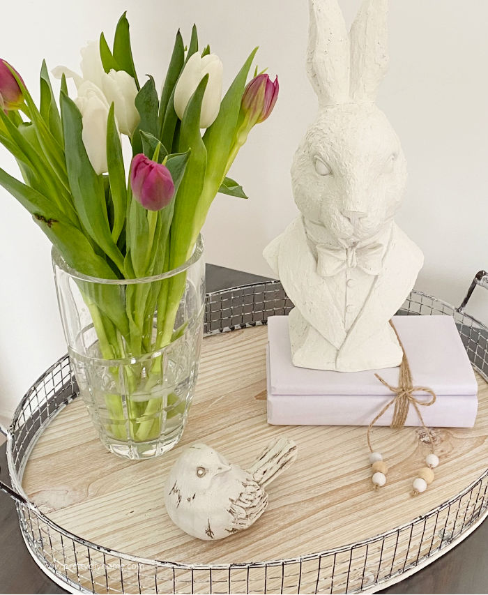 A Spring vignette featuing a crystal vase full of fresh cut tulips, a clay bird, white books tied with twine and an Easter bunny.