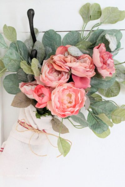 A pink Ikea Flower arrangement with greenery, wrapped in a bundle and tied with twine. A pretty farmhouse flower arrangment you can use for Valentines day or into Spring.