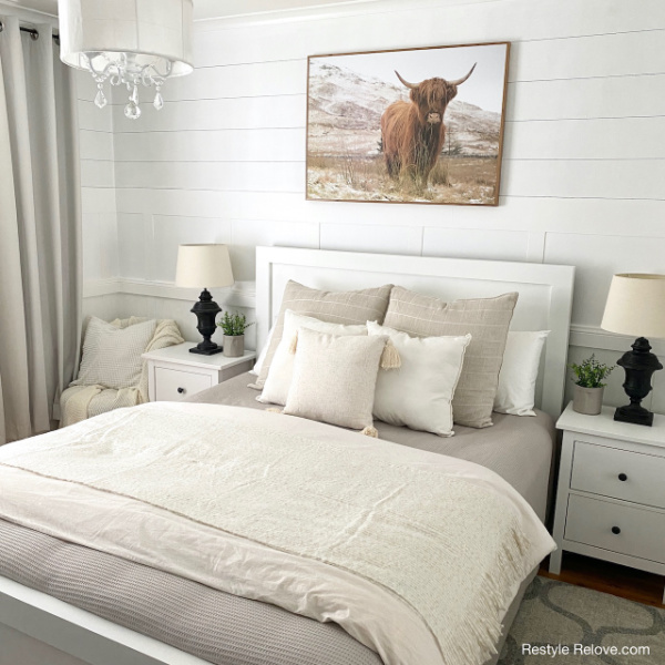 A neutral farmhouse bedroom makeover in creams and whites, with black lamps