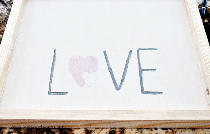 hand painted word LOVE on a dollar store frame with natural sides and white background