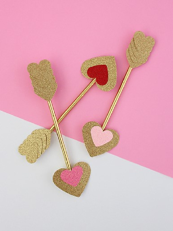 Three pink and gold Valentine arrows with pink valentines.
