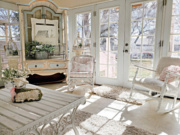 A farmhouse vignette with a white barn in a large white armoire. The room is decorated in white and pink with lots of bright and sunny windows.