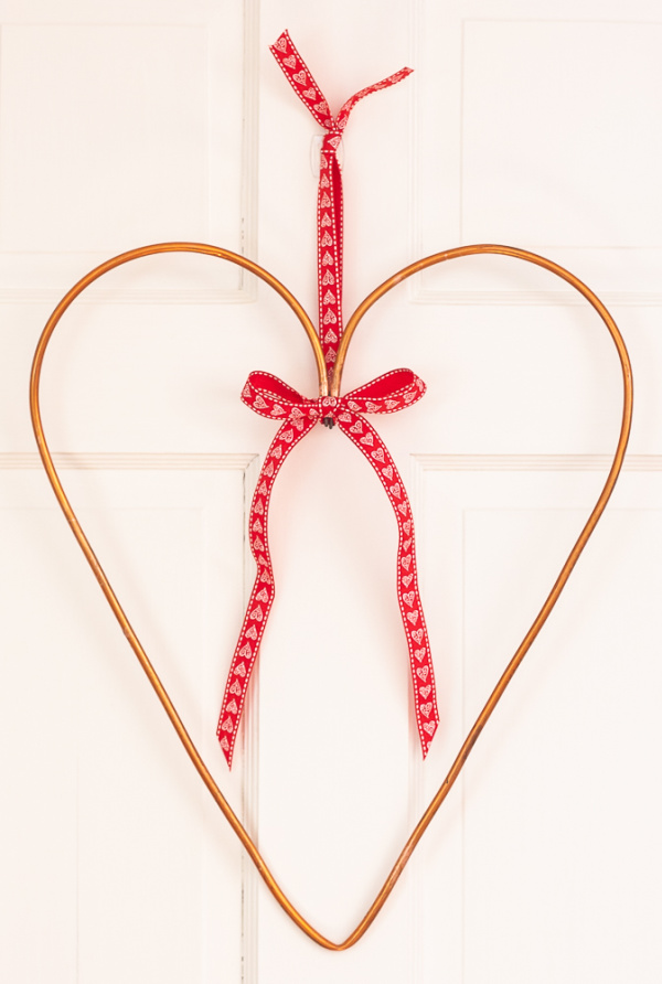 Handmade copper pipe Valentine hanging on a door with pretty red ribbon.