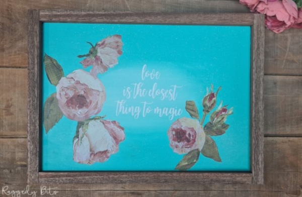 A DIY vintage looking farmhouse sign with a blue background and pink roses.