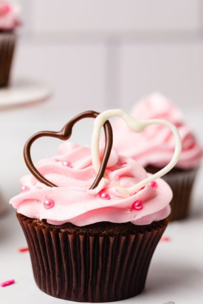 Chocolate Valentine cupcakes made with heart shaped swirls of chocolate Valentines on top.