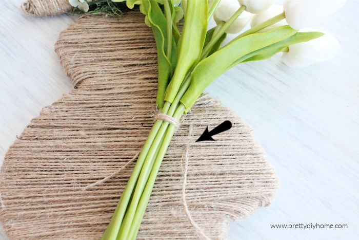 Weaving twine through other twine to attach tulips to a wooden twine covered Easter Bunny craft.