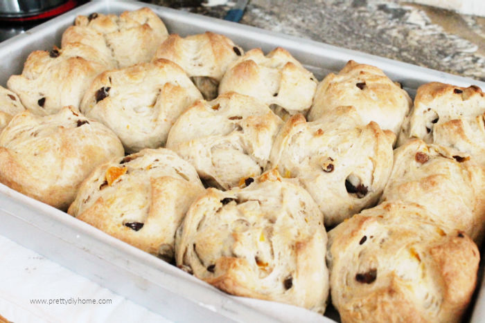 A large pan full of just out of the oven fresh hot cross buns, that are golden brown and show little bits a apricot and raisins in the dough.