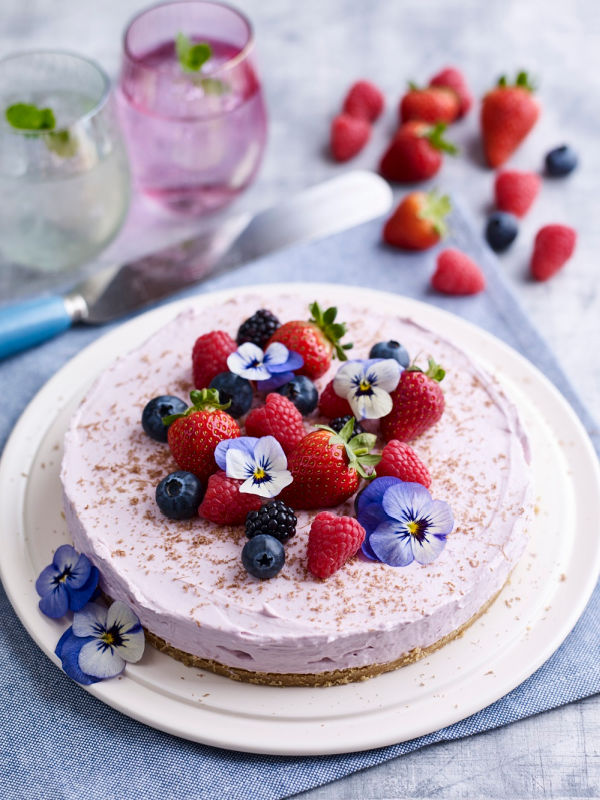 A small homemade berry cheesecake with fresh berries and pansie blossoms on top.