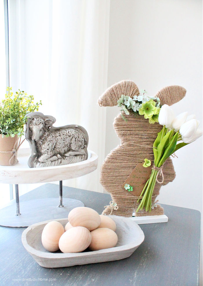 A neutral farmhouse Easter bunny made with twine and faux flowers. He is sitting beside a small bowl full of natural wooden eggs, a vintage sheep chocolate mold and a farmhouse tray.