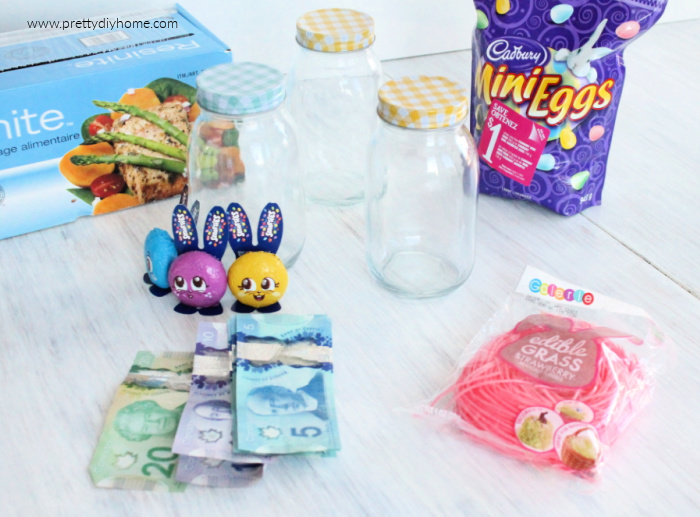 The supplies needed for making a DIY E gift for tweens or older kids, including money, mini chocolate eggs, a small jar and mason jar.
