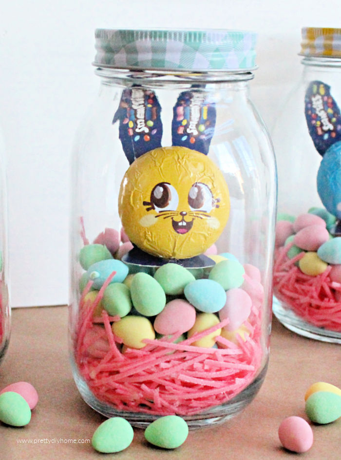 A single DIY Easter Mason jar gift idea with cash and layers of colourful candy, including a small chocolate Easter bunny.