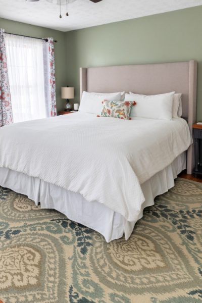 A large upholstered headboard in a bedroom with green carpet and walls.