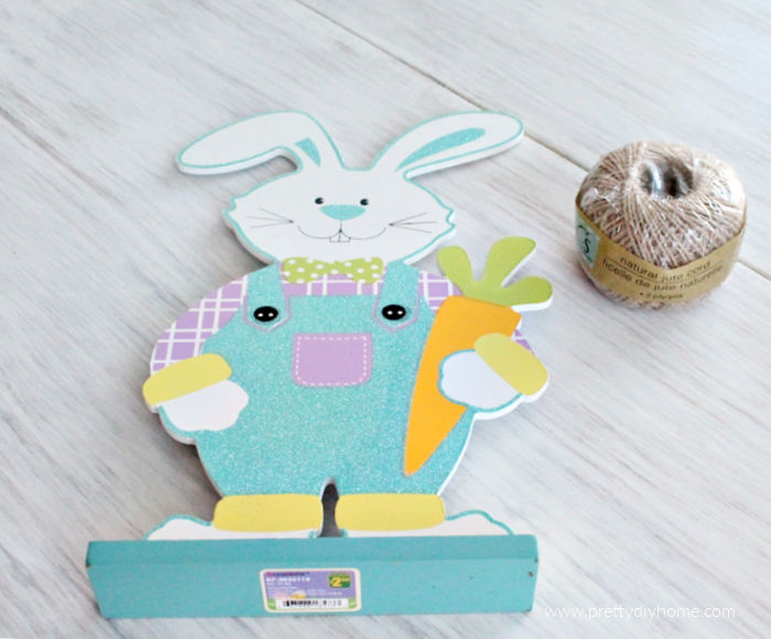 Bright male wooden Easter bunny from the dollar store with glitter. He has soft blue overalls, a white and blue face, and a painted orange carrot.