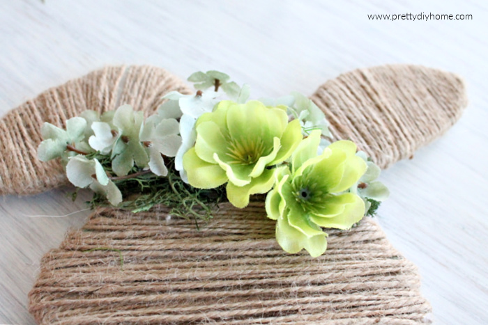 Making a floral crown for a Easter bunny using moss, soft green flowers for the background. and two large bright green flowers for a focal point.
