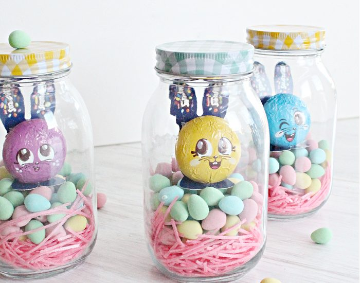 Three Easter mason jar ideas for children, each mason jar is filled with pink candy grass, colourful chocolate mini Easter eggs, and a small Easter bunny. The inside has a cash gift included.