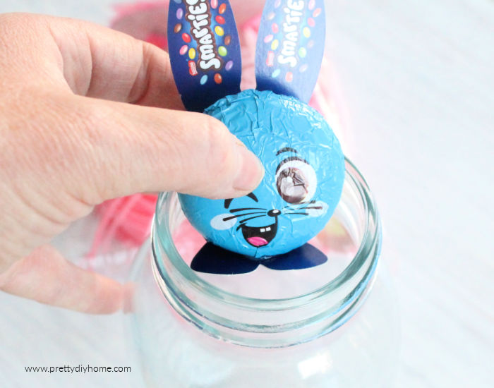 A small chocolate foiled wrapped Easter bunny with paper ears, being placed inside the rim of a mason jar. The image is to illustrate awareness of the Easter bunnies size when purchasing.