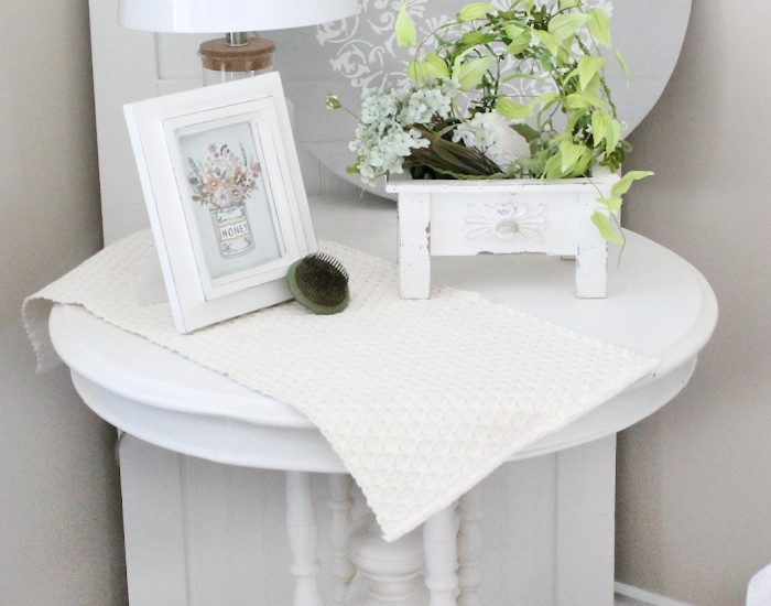 An old drum table refinished with white and cream paint, and then decorated with pretty neutral farmhouse decor.