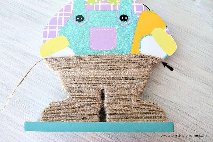 Wrapping a dollar store Easter bunny in twine for neutral farmhouse Easter decor.