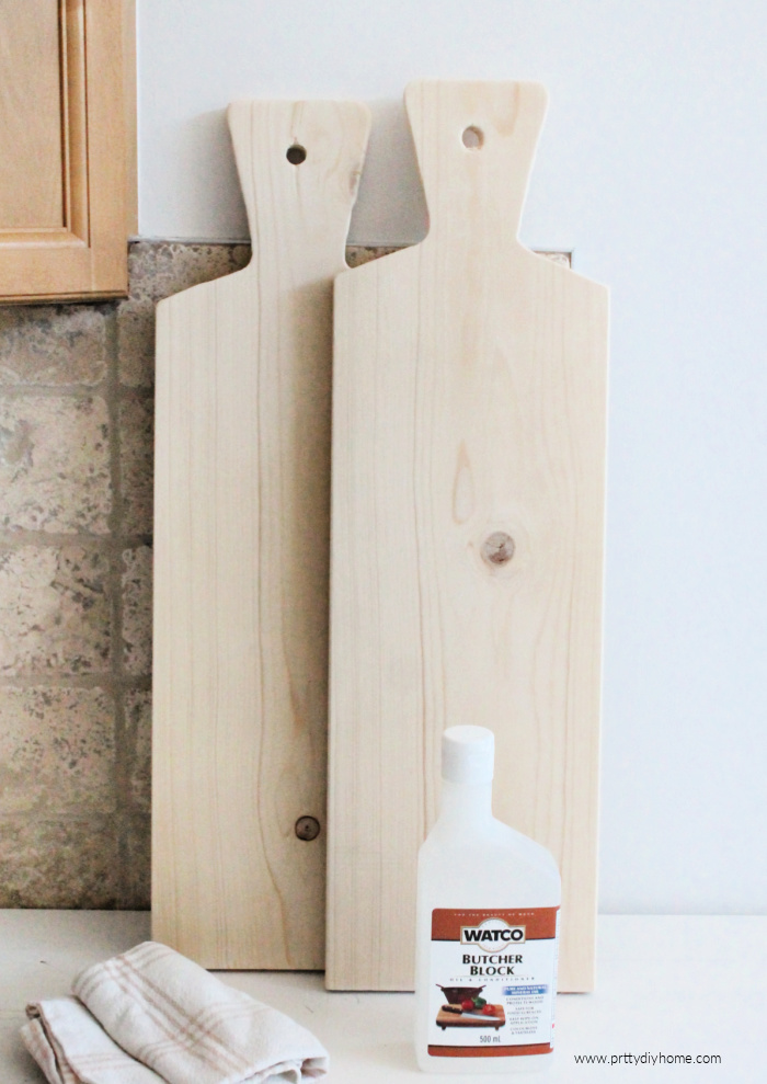 Two tall wine bottle shaped wood charcuterie boards, along with butcher block mineral oil for sealing the wood