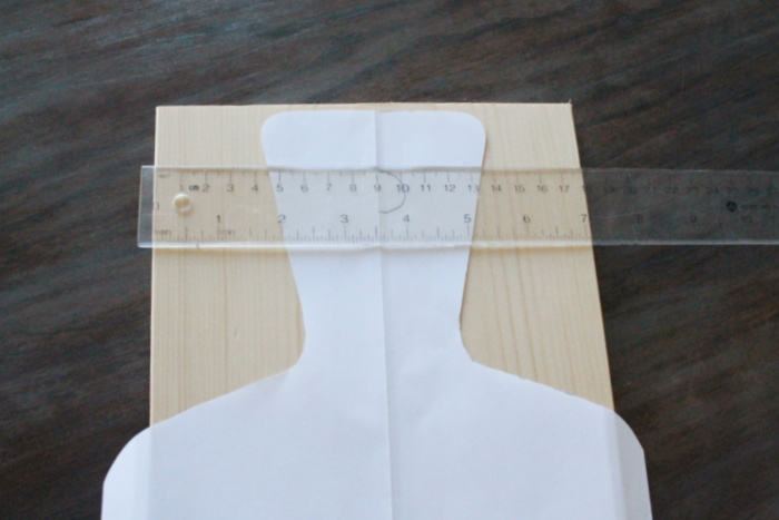 A piece of lumber with a cut out pattern for a charcuterie board handle. There is a ruler vertical across the top of the wood to center the pattern evenly.