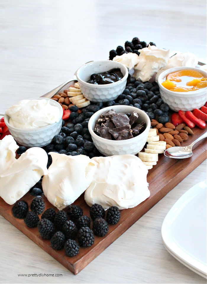 Pavlova grazing platter with mini pavlova, fresh fruit and whipping cream, along with assorted toppings like chocolate.