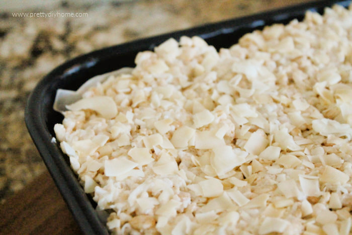 A large tray of layered rice krispie treats with coconut and almonds The squares are cooling in a large black pan and have not been cut yet.