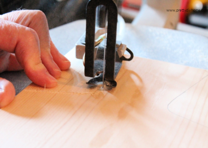 Using a scroll saw to cute out the handles on a wine bottle shaped Charcuterie Board.