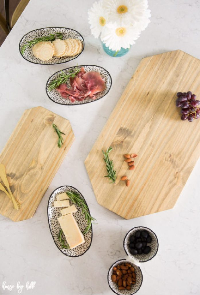 Two easy to make DIY charcuterie boards surrounded by trays full of meat and cheese.