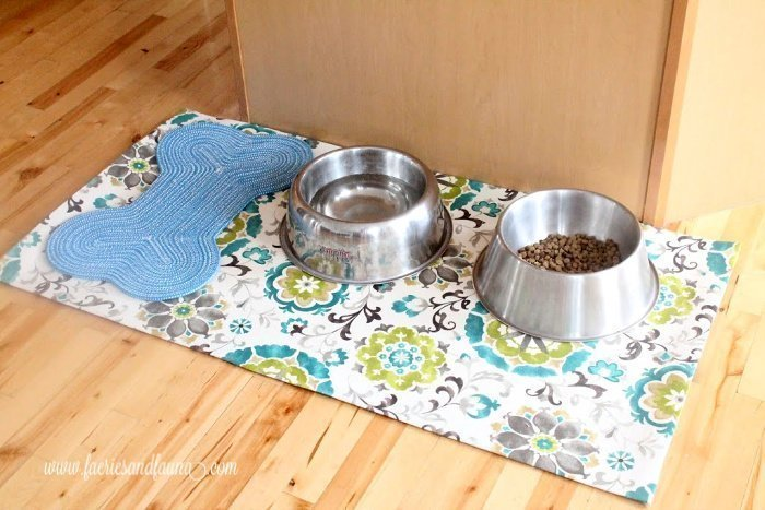 A DIY waterproof feeding mat for pets, The pet placemat is very large, covered in pretty blue, green, and teal fabric, with two large pet food bowls and a small fabric bone cloth placemat for snacks.