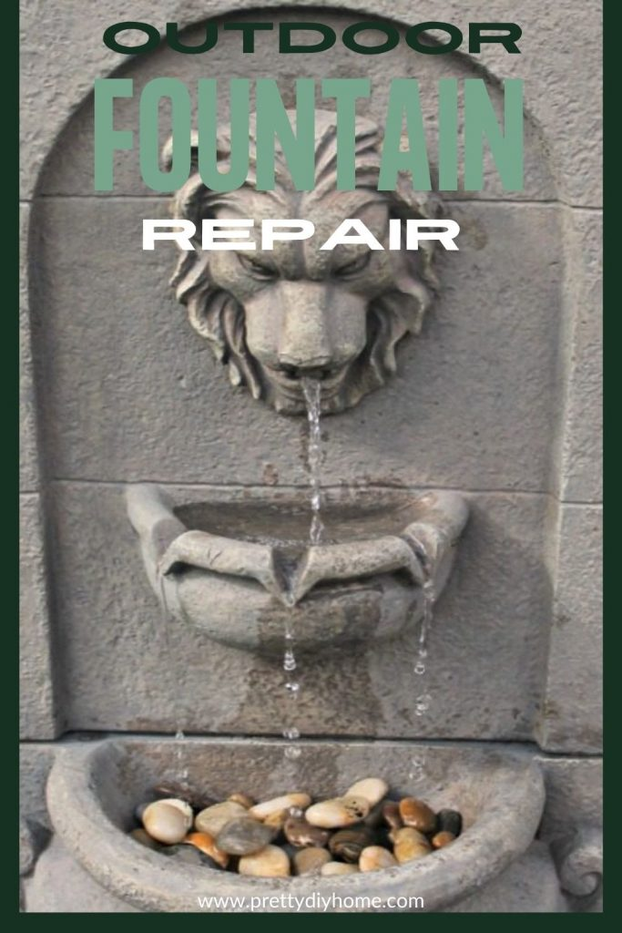A repaired outdoor fountain, its a large resin lion fountain with water dropping down to a small basin with plants and rocks.