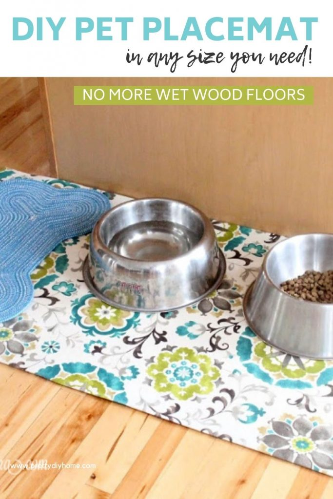 A large waterproof homemade dog feeding area placemat. The fabric is a pretty green and bright blue, and there are two large dog bowls on top.