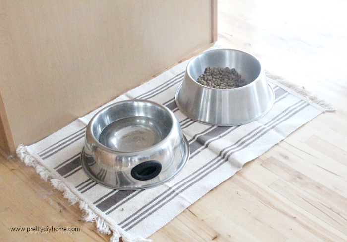 A neatly arranged dog pet food area, but the floor can get damaged by water from a pet bowl.