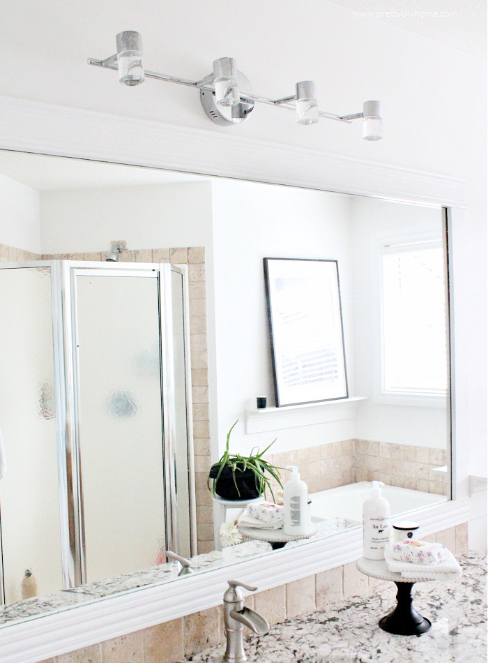 A large builder grade mirror updated with white farmhouse moulding in a master bathroom