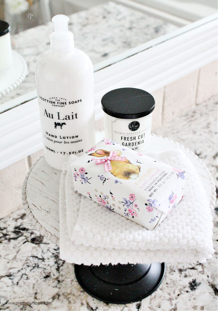 Bathroom handsoap, facecloth, candle and hand lotion sitting on a black and white tiered tray.