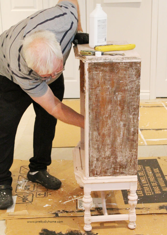 A man stripping blush coloured chalkpaint from a pink blush painted solid wood furniture.
