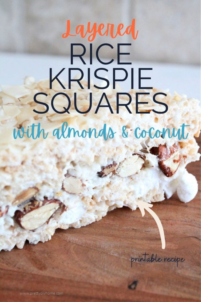 A cut slice of rice krispie treats showing a center with almonds, coconut, and whole marshmallows.
