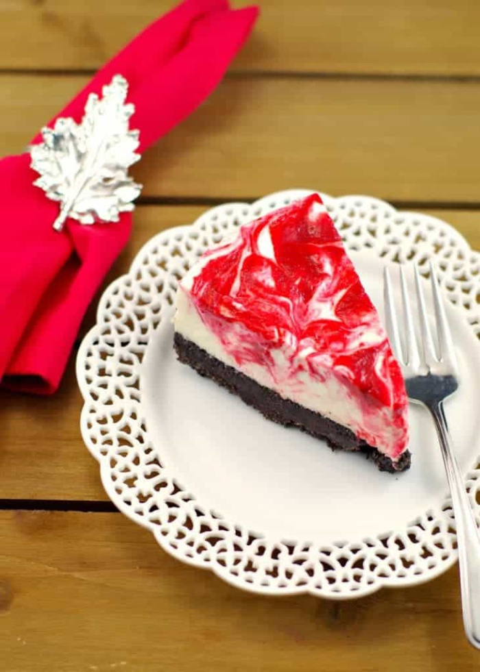 A slice of light rhubarb cheesecake with a chocolate cookie crumb crust, no bake cheesecake filling, andd covered with sweet rhubarb topping. An easy to make no bake dessert recipe.