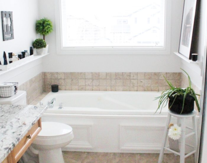 A master bath with large soaker tub, shelves, and farmhouse decor. A builder grade bathroom makeover that can be done quickly and on a budget.