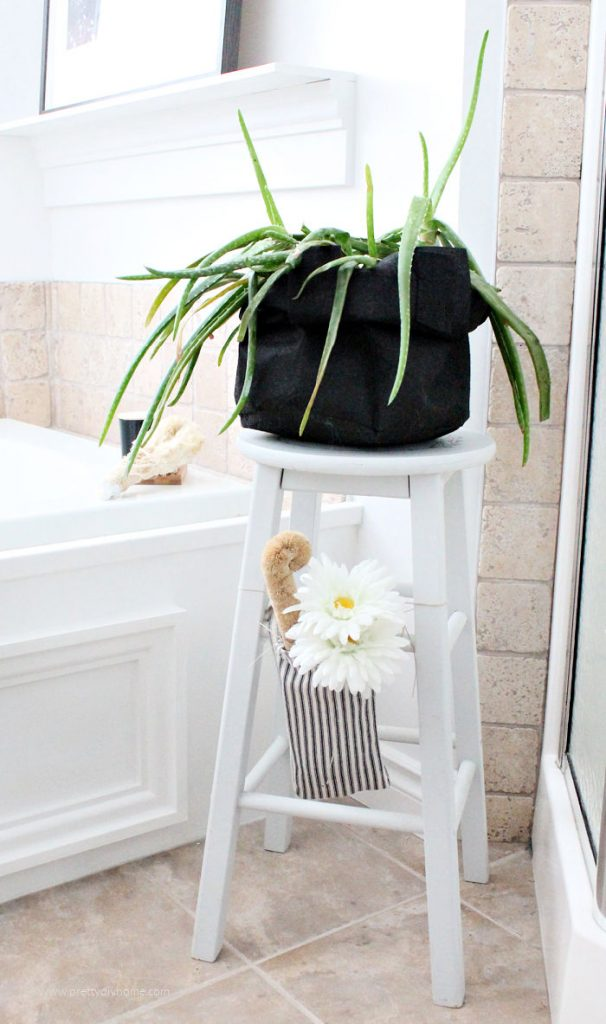 Farmhouse plantstand for the bathroom with an aloe vera plant on top and a scented farmhouse bag with a flower hanging on the side.