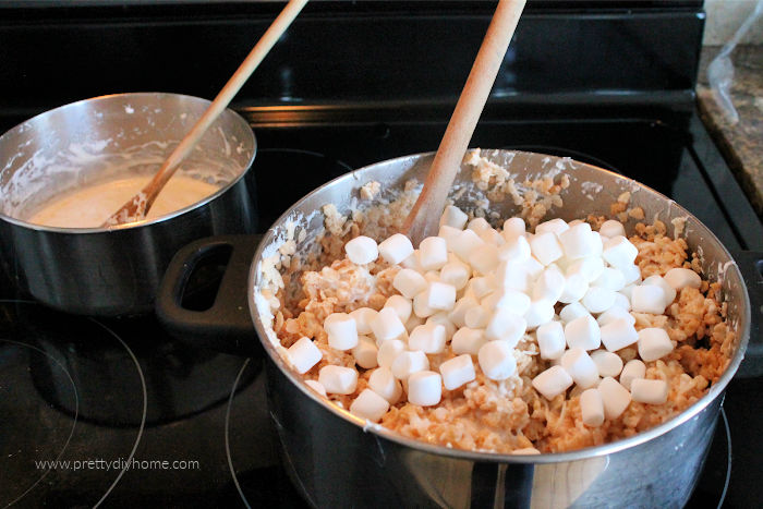 Mixing together coconut, rice krispies and marshmallows for a no bake square.