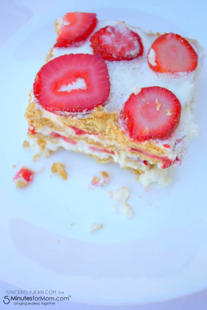 A no bake dessert recipe made with strawberries, and layers of puffed pastry. The cake is served in a large square piece on a white plate.