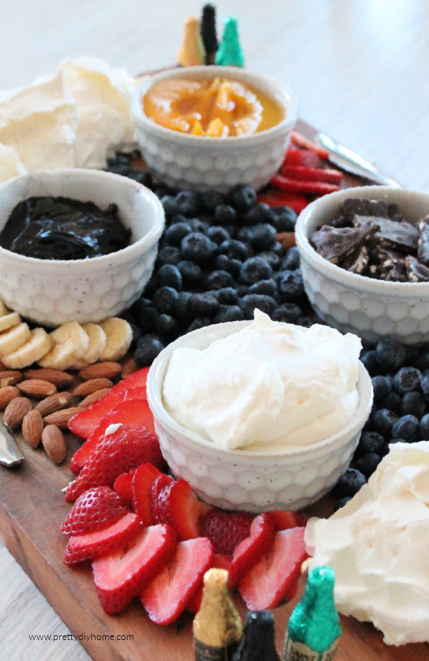 A pavlova charcuterie board with a palova recipe, strawberries, whipping cream, blackberries, blueberries, chocolate and fresh fruit.