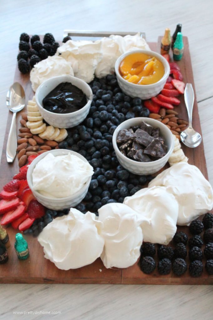 A large wood charcuterie board with homemade mini pavlova, blackberries, strawberries, blueberries, bananas, almonds, peaches and chocolate liquere bottles.