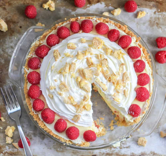 A large whole red raspberry lemon dream pie no bake dessert recipe. This no bake dessert is made in a large pie plate with a cookie crust, lemon filling, whipped topping with crumbled cookies, and encircled with fresh red raspberries.